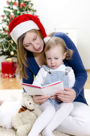Girl and her mom reading book at Christmas Stock Photo - 11413192