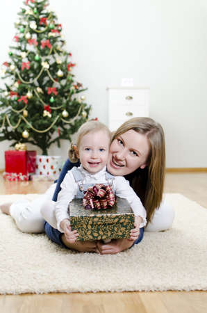little girl and her mother holding gift at Christmas Stock Photo - 11413194
