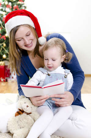Girl and her mom reading book at Christmas Stock Photo - 11413193