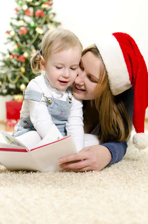 Girl and her mom reading book at Christmas Stock Photo - 11413186