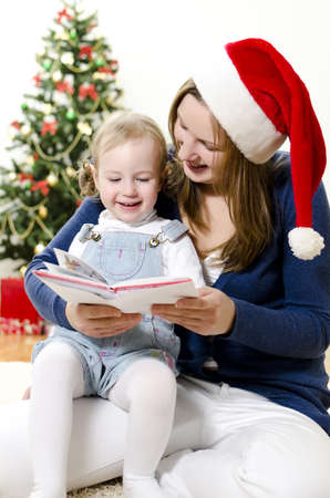 Girl and her mom reading book at Christmas photo