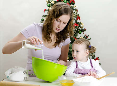 little girl and mother are preparing Christmas cookies photo