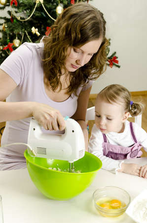 little girl and mother are preparing Christmas cookies Stock Photo - 11413223