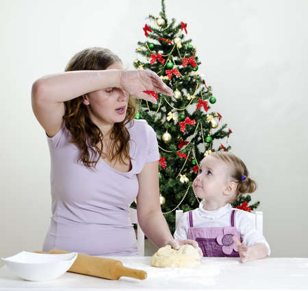 little girl and mother are preparing Christmas cookies, Mom seems to be tired photo