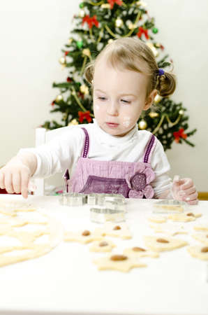 little cute girl making Christmas cookies photo