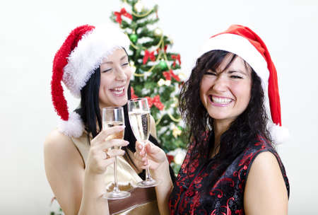 Christmas: two girls in red hat have fun Stock Photo - 11688285