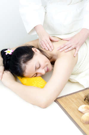 Young lady receiving back massage at spa center photo