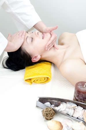 Young lady receiving face massage at spa center photo