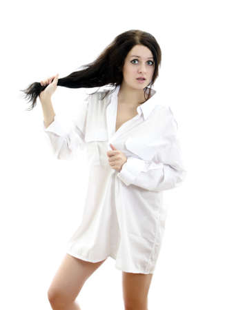 Sensual brunette girl in mans shirt touching her hair. Isolated on white. photo