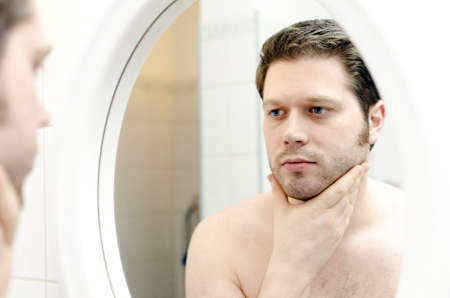 body grooming: Man looks at his beard and thought about shaving Stock Photo