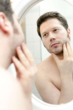 Man looks at his beard and thought about shaving photo
