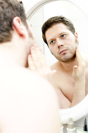 mirror face: Man looks at his beard and thought about shaving Stock Photo
