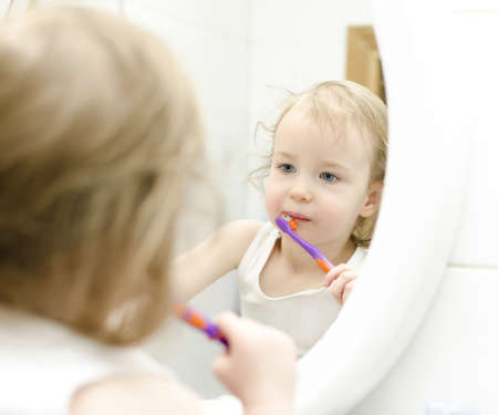 Little girl brushing her teeth in bathroom photo