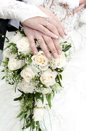 Bridal bouquet of flowers with hands of newlyweds photo