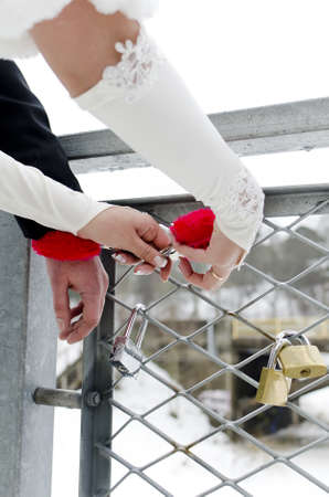 fastens: Newlyweds with handcuffs. Bride fastens groom with handcuffs. Stock Photo