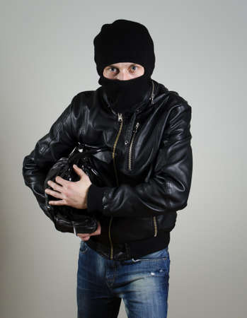 Portrait of male burglar with a handbag. photo