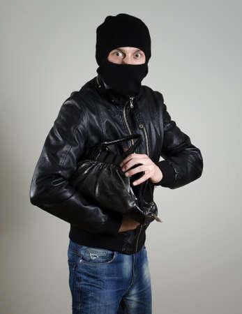 Portrait of scared male burglar with a handbag. Stock Photo - 12879321