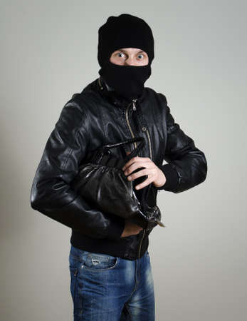 Portrait of scared male burglar with a handbag. photo