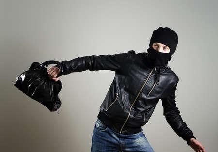 snatched: Portrait of running male burglar with a handbag.