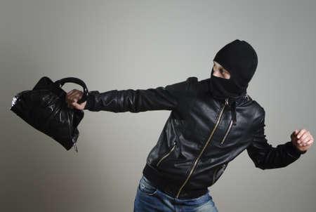 arracher: Portrait de courir cambrioleur m�le avec un sac � main. Banque d'images