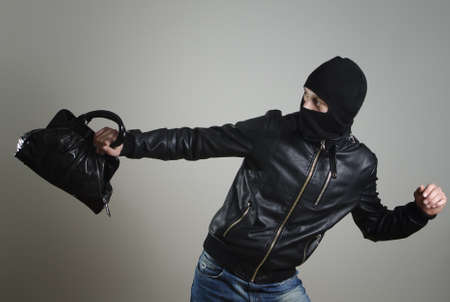 Portrait of running male burglar with a handbag. photo