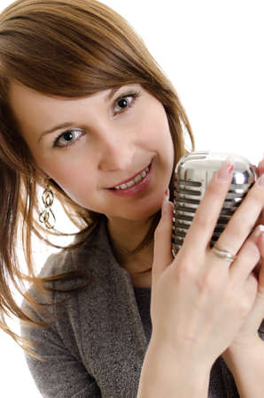 Young woman holding a retro-microphone  Isolated on white  photo