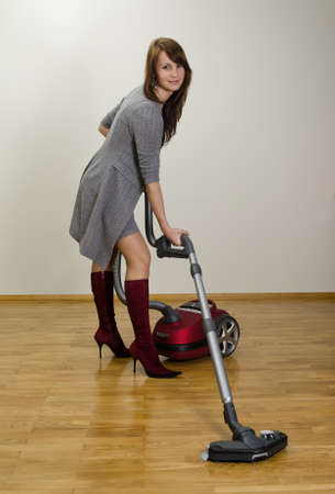Attractive smiling girl with red vacuum cleaner  photo