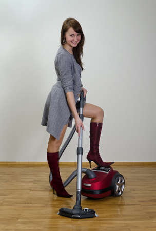 Attractive smiling girl with red vacuum cleaner