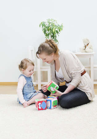 Mother and daughter playing in the childrens cubes photo