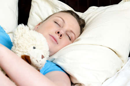 Young girl fell asleep with teddy bear photo