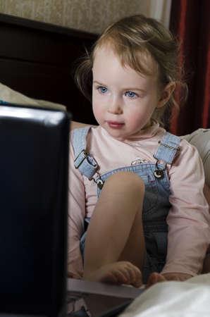 Little girl looks cartoon on the laptop photo
