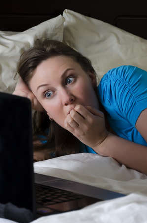 suspense: Young woman scared while watching movie in dark room Stock Photo