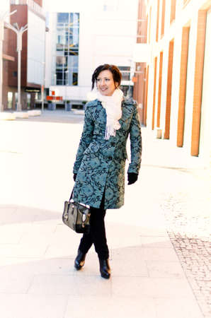 Pretty smiling girl in coat standing outdoors  photo