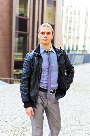 Portrait of successful young guy against urban background photo
