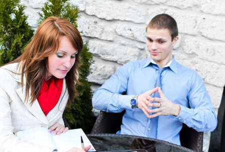 Business partners meeting: Male and female sitting outdoors. Focus on female. photo