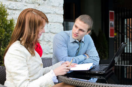 Business partners meeting: Male and female with laptop sitting outdoors photo