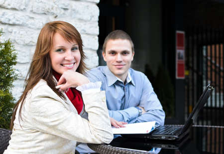 Business partners meeting: Male and female sitting outdoors. Focus on female. Stock Photo - 13407381