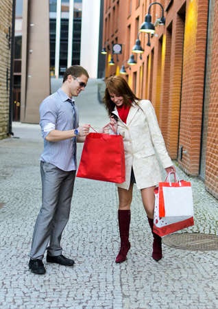 Smiling female shows purchases to male photo
