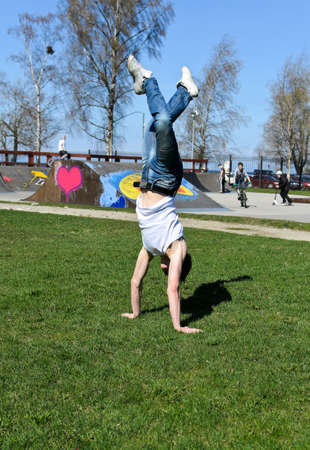 Breakdancer doing a flip on the grass. photo