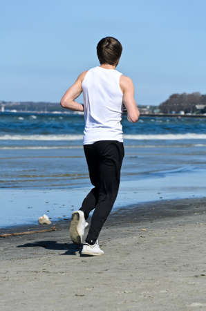 Athletic young male running on the beach  From the back photo