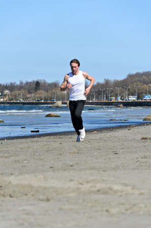 Athletic young male running on the beach photo