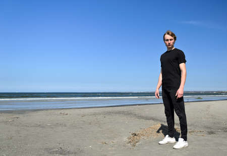 Young male in black clothes and white shoes standing on the beach Stock Photo - 13488858