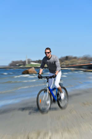 Motion blur  male riding a bicycle by the sea photo