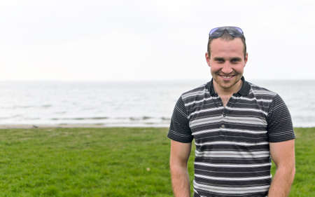 Handsome smiling man near the seaside. Stock Photo - 13559177