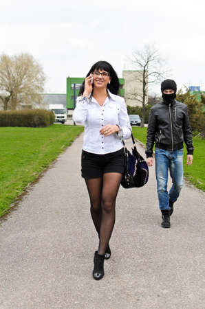 mugger: Robber follows his victim at daylight on the street Stock Photo