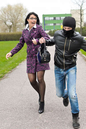 Daylight robbery on the street. Thief steals a bag. Stock Photo - 13559235
