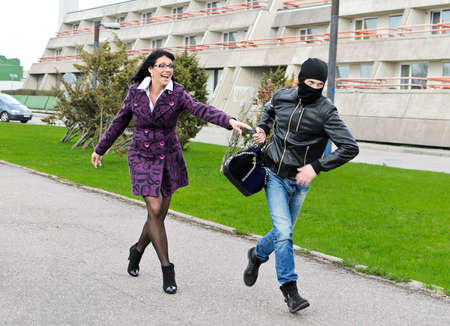 Daylight robbery on the street. Thief steals a bag. Stock Photo - 13559180