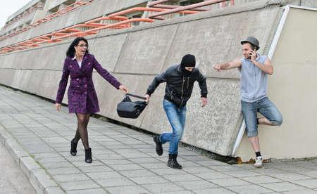 beroofd: Diefstal preventie op straat. Dief probeert om een tas te stelen. Stockfoto