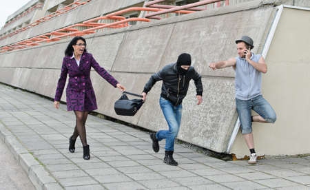 Robbery prevention on the street. Thief try to steal a bag. photo