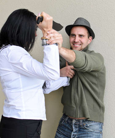 Woman is trying to kill man by knife. photo